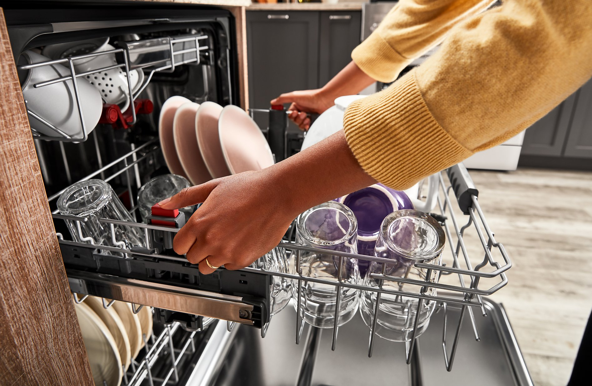 Hands pulling out 2nd rack of a third rack dishwasher