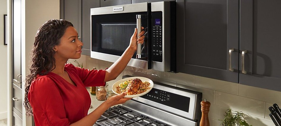 Woman placing food into an over-the-range microwave