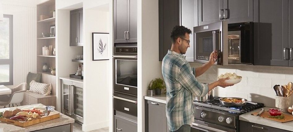 Man placing dish in an over-the-range microwave