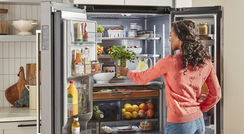 Woman in pink sweater putting herbs in French door type of refrigerator