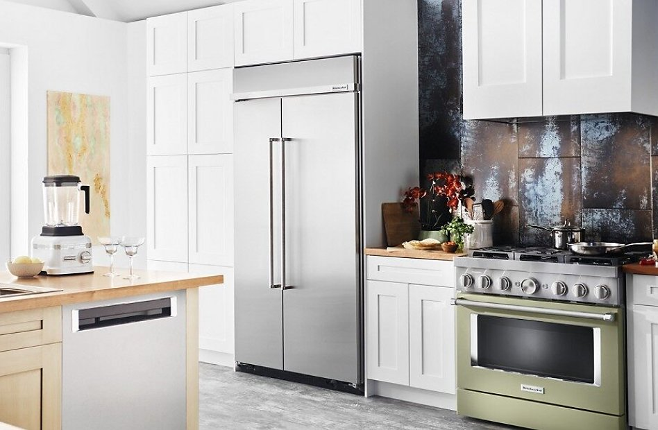 Built-in refrigerator style installed in white cabinets in modern kitchen