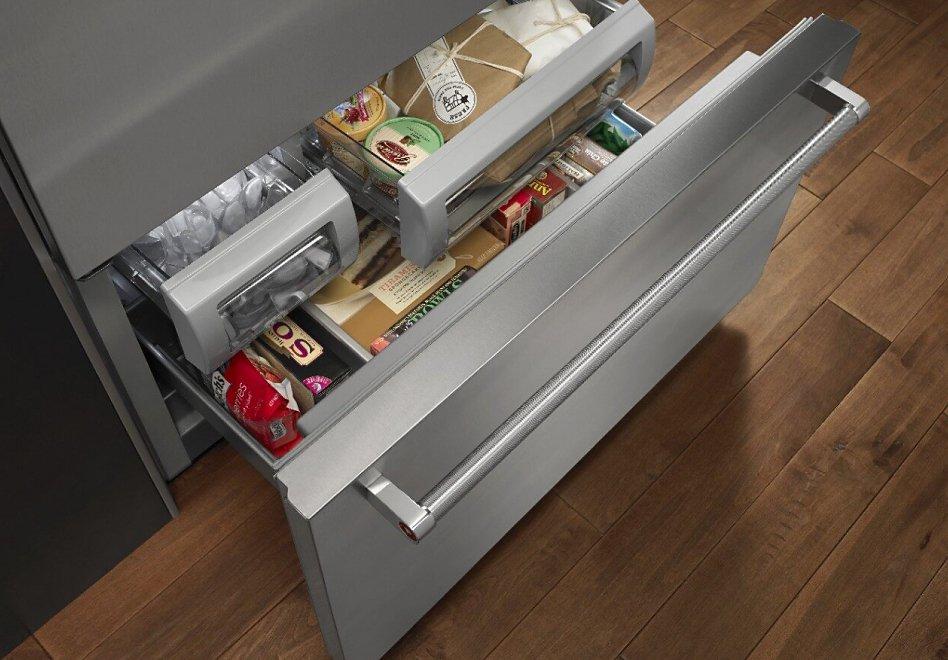 Open bottom freezer refrigerator drawer with food inside