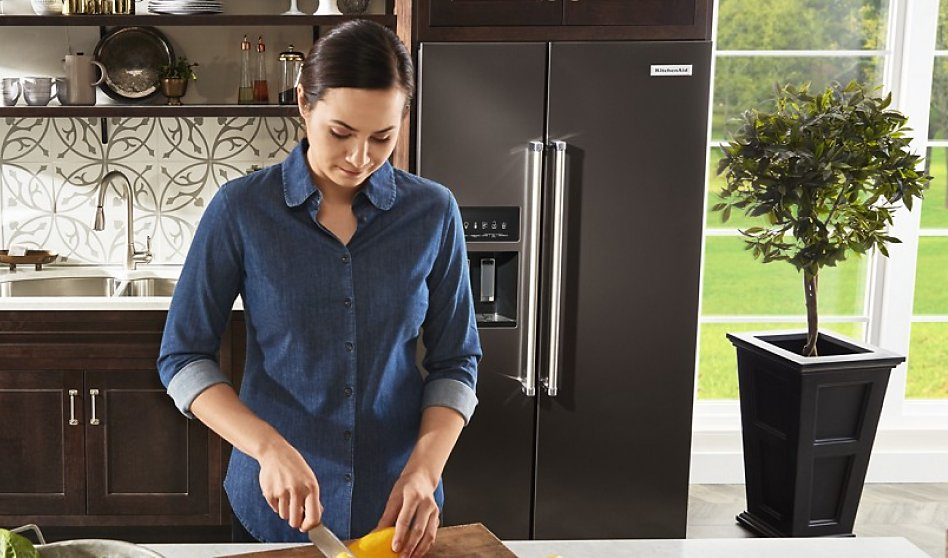 Woman preparing food in front of side-by-side fridge type in modern kitchen