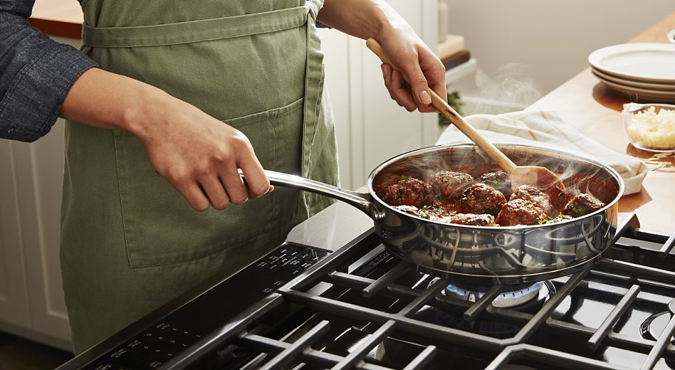 A person simmering meatballs on a stovetop