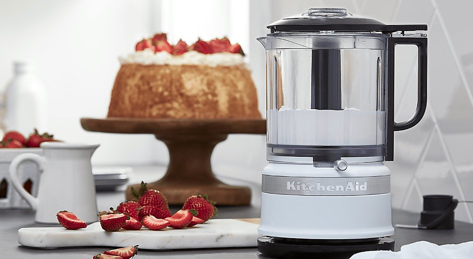 A KitchenAid® food processor in front of a cake topped with strawberries