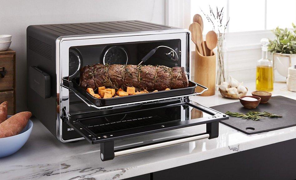 Roast beef on pan inside open convection countertop oven