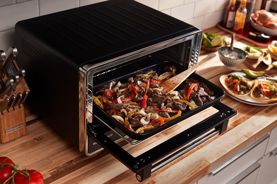 Fajita ingredients on pan inside open countertop oven