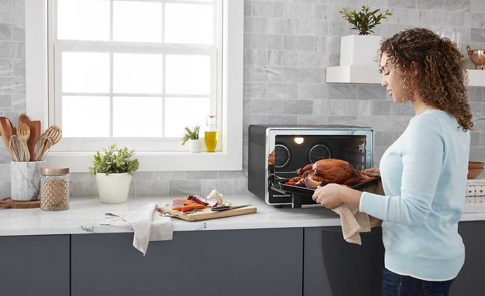 Woman removing roast chicken from open countertop oven