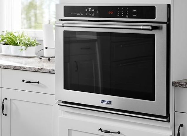 A Maytag wall oven installed in a white kitchen.