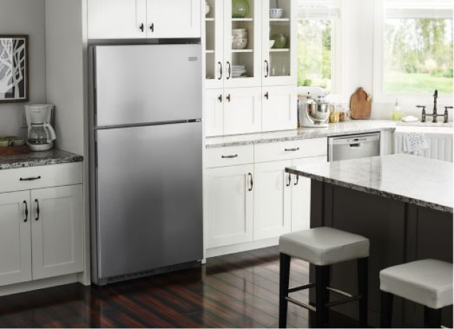 A Maytag stainless top freezer refrigerator in a white kitchen.