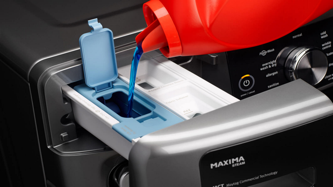 Filling a Maytag® washing machine dispenser with detergent.