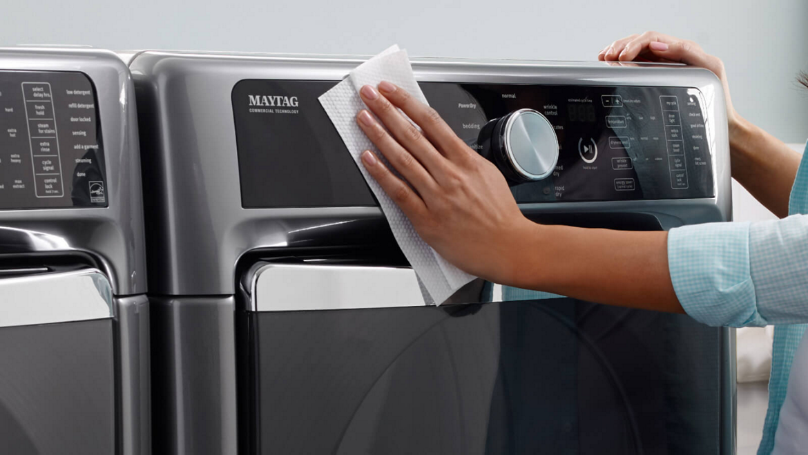 A woman cleaning the outside of a Maytag ® front-load washer.