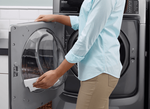 A woman cleaning the inside of a Maytag® front-load washer.