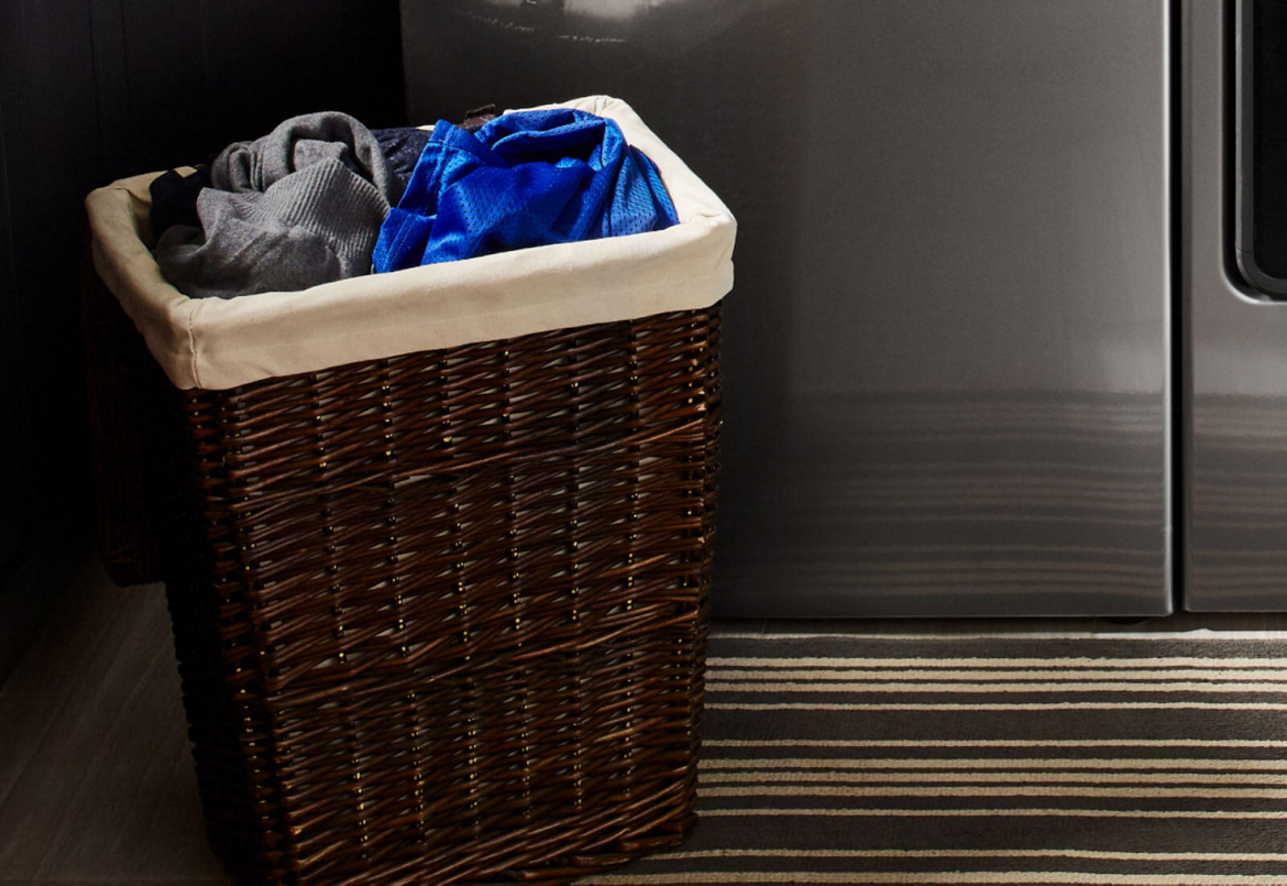 A hamper filled with laundry sorted by color.