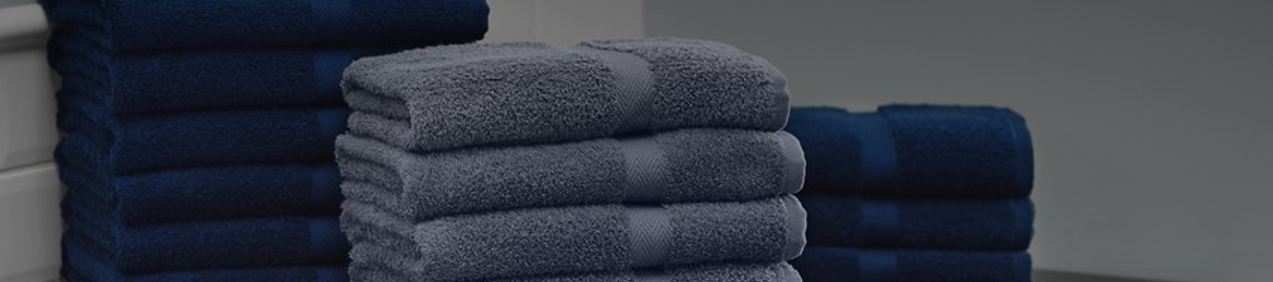 Folded blue and gray bath towels stacked in three separate piles.