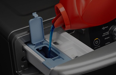 Pouring laundry detergent into a Maytag® detergent dispenser.