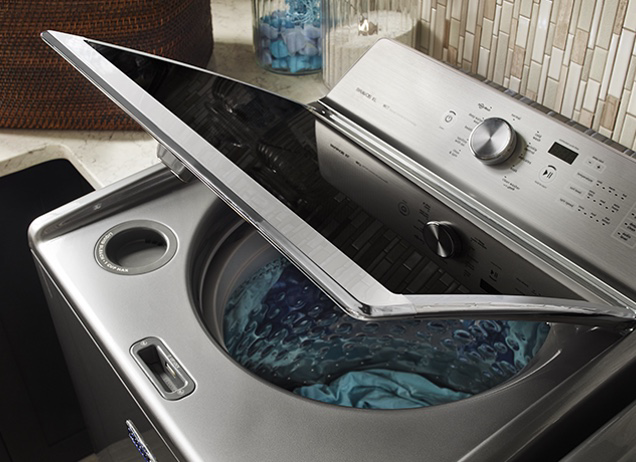 A Maytag® top-load washing machine with its lid open.