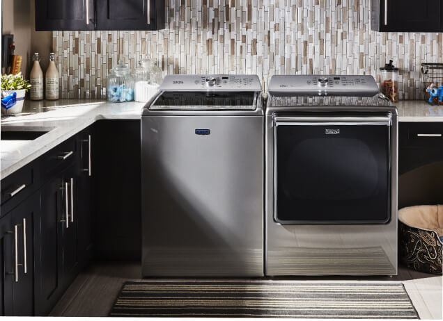 A metallic slate Maytag® washer and dryer pair in a modern laundry room.