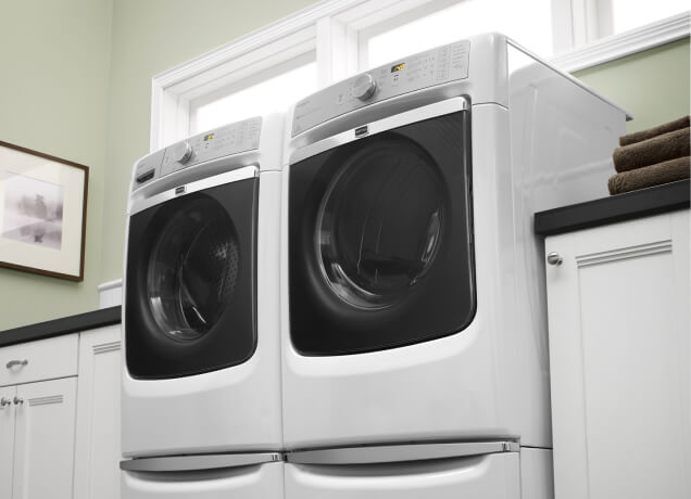 A white Maytag® front-load washing machine and dryer resting on laundry pedestals.