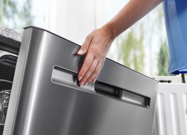 A hand closing a Maytag dishwasher