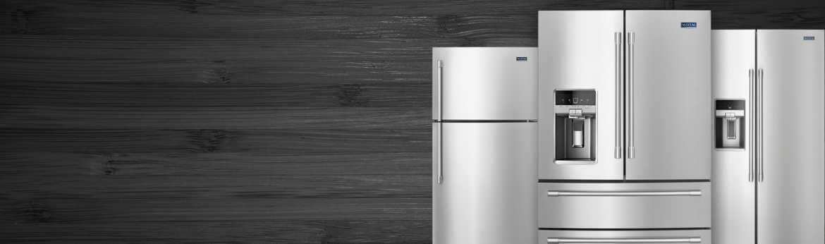 Three stainless steel refrigerators set against a charcoal grey wood background.