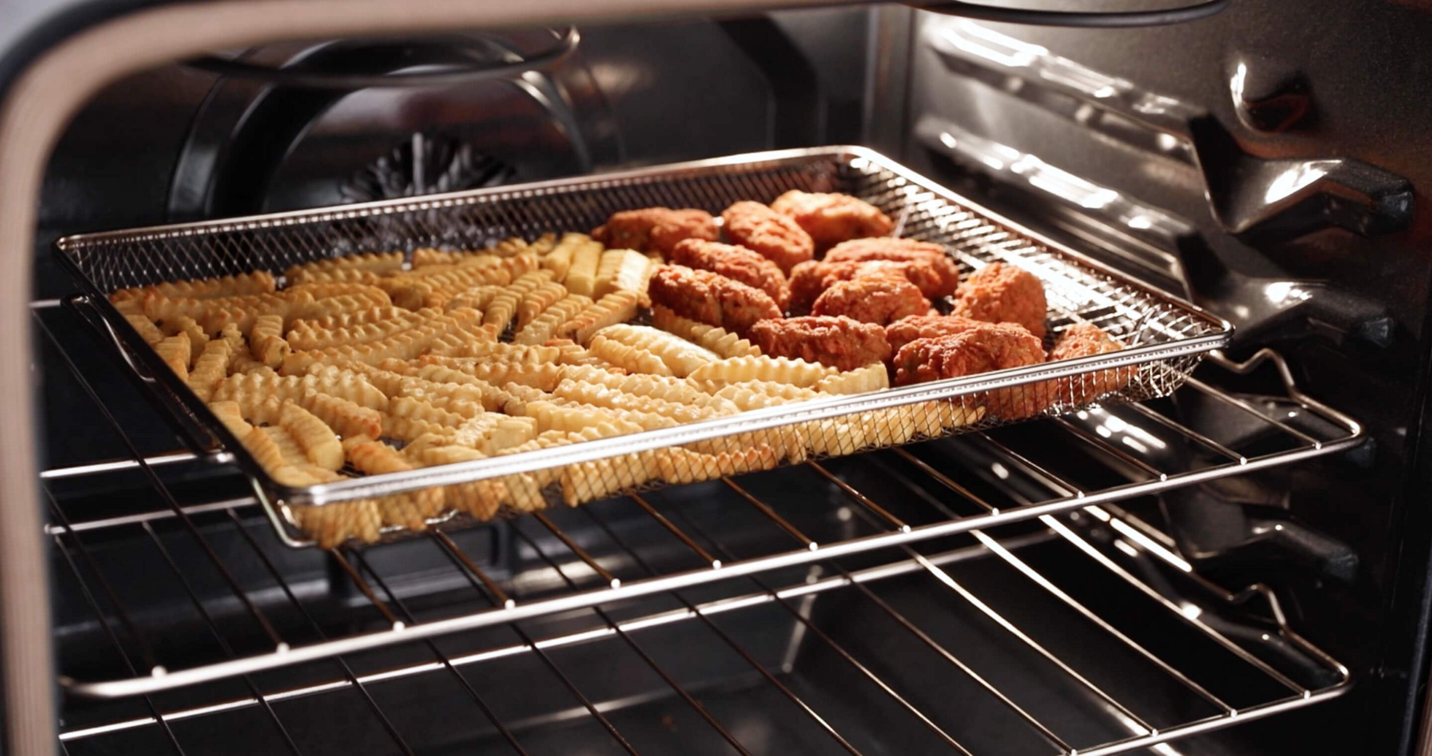 Fries and chicken wings in the dishwasher-safe air fry basket.
