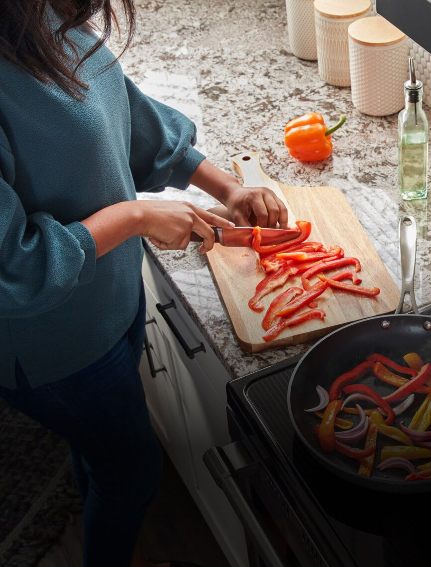 A woman chopping up vegetables on her countertop.