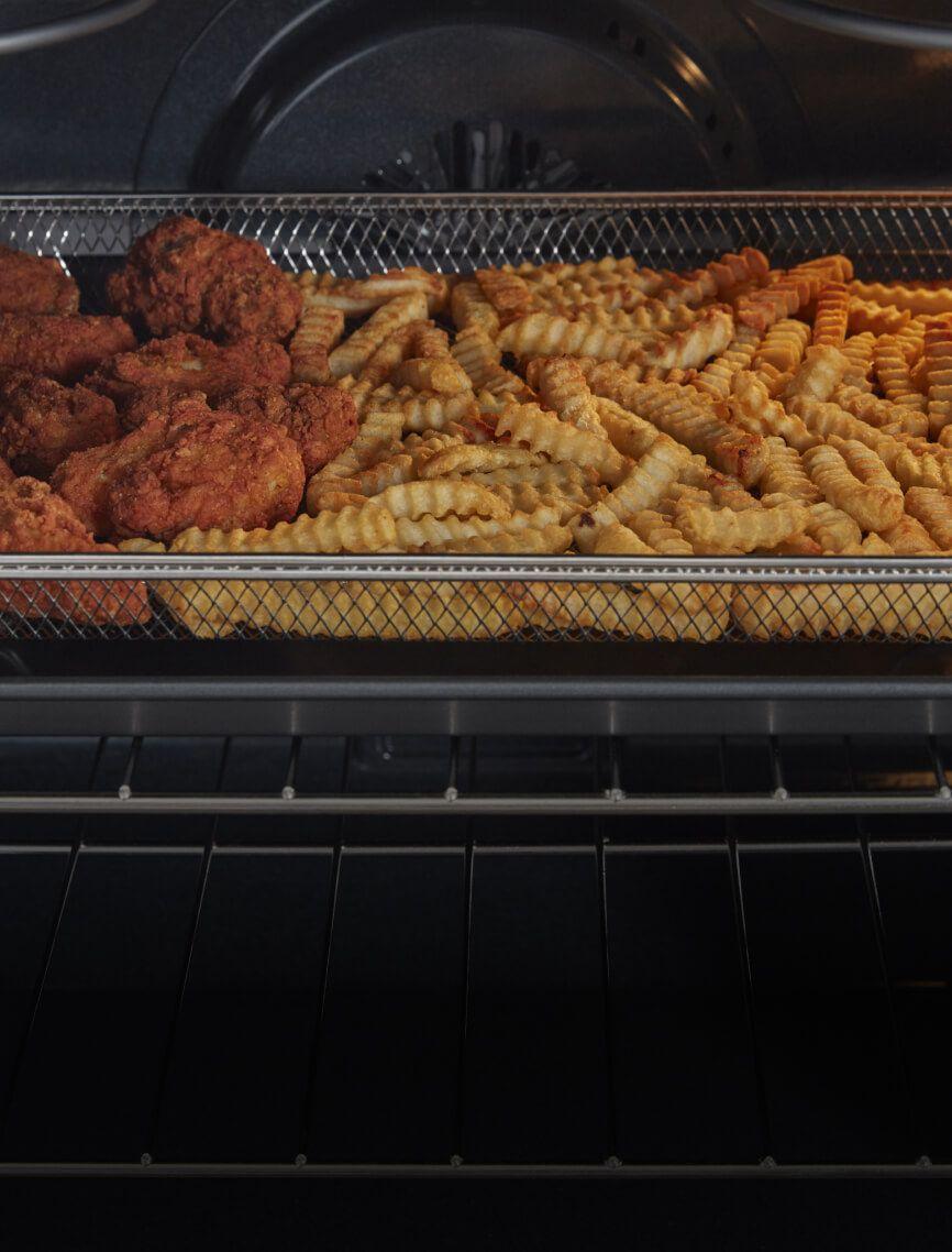 Chicken wings frying in the air fry basket.