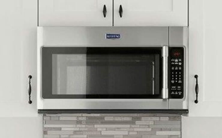 Stainless steel over-the-range microwave in a kitchen.