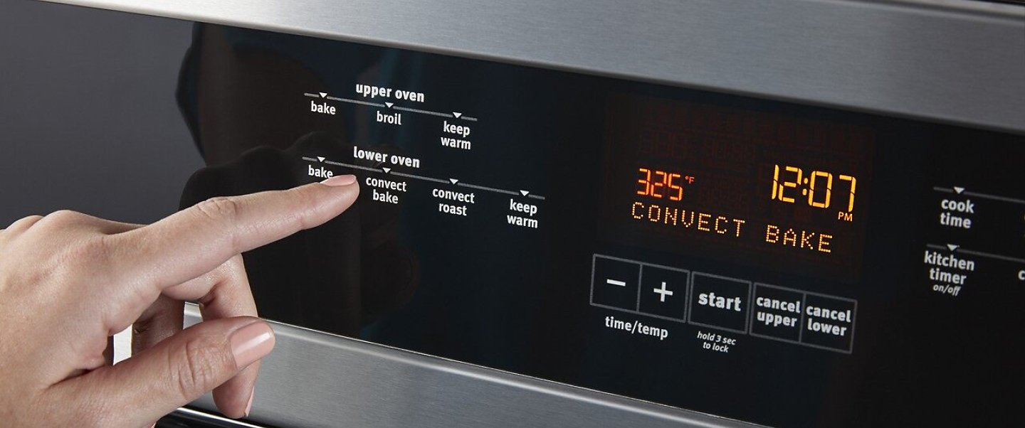 Person selecting an option on a wall oven console