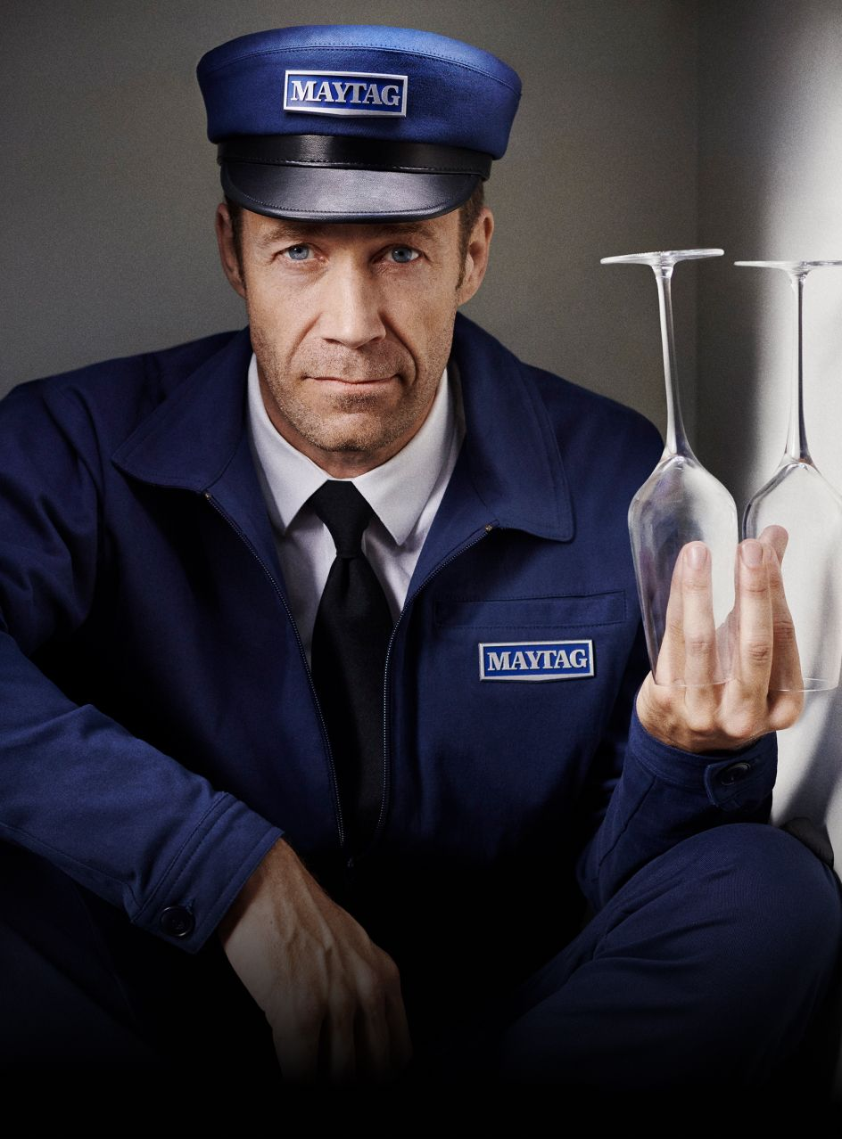 Maytag man holding champagne flutes.