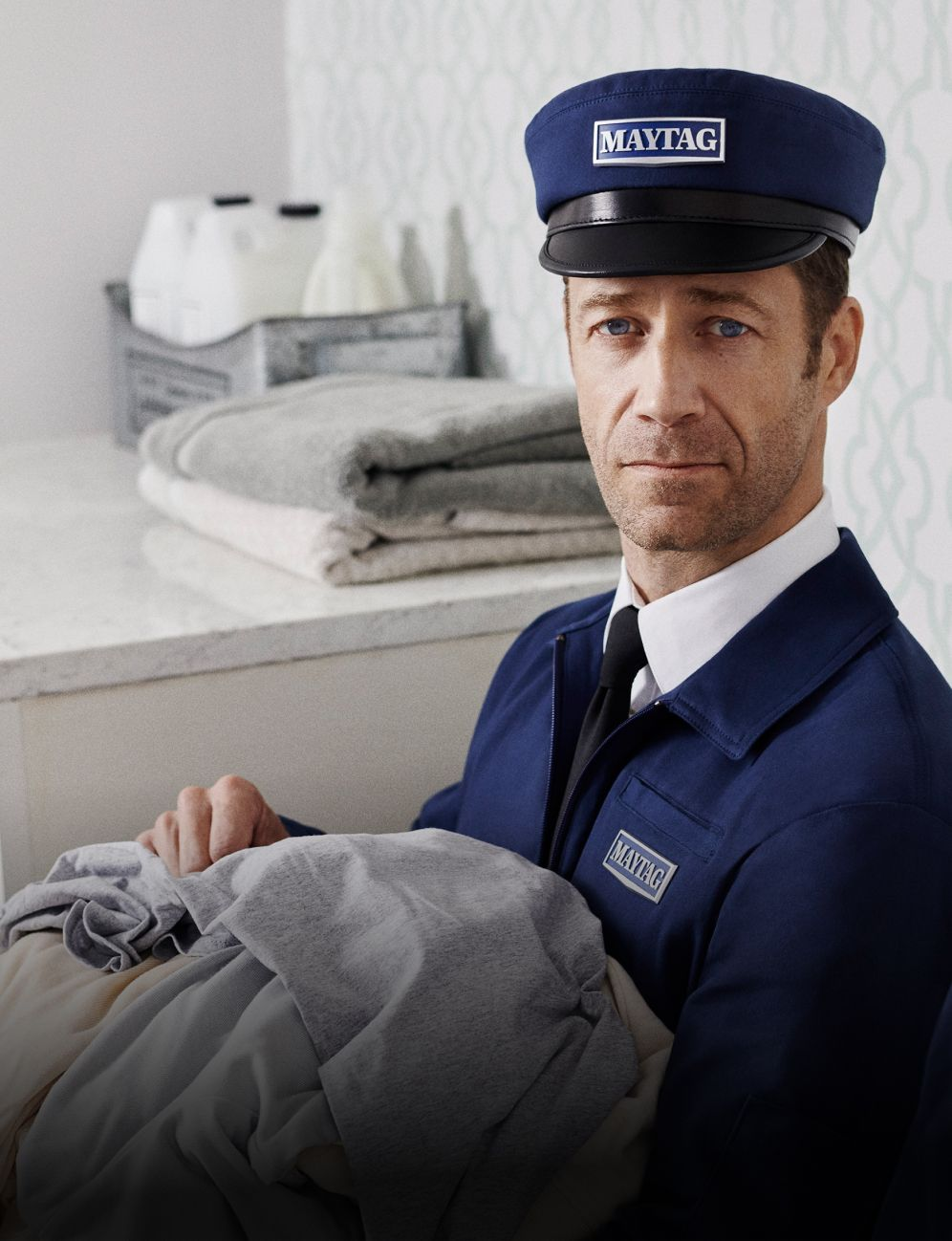 Maytag man holding clothes.