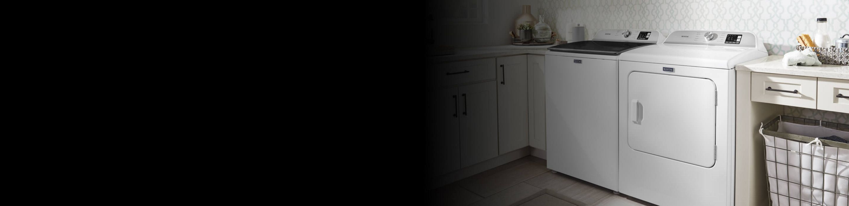 White Maytag® washer and dryer pair in laundry room.