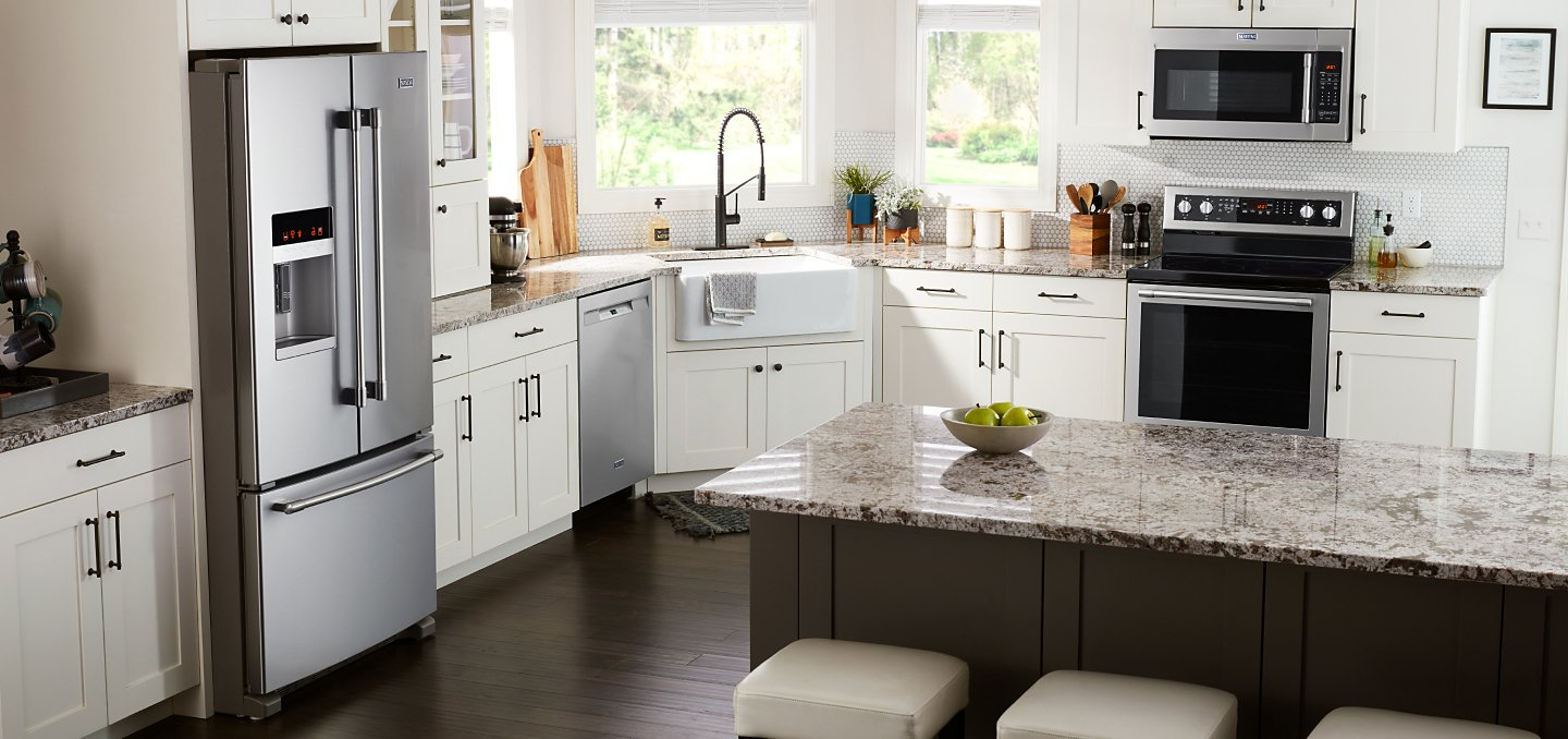 Stainless steel Maytag® appliances in a white kitchen