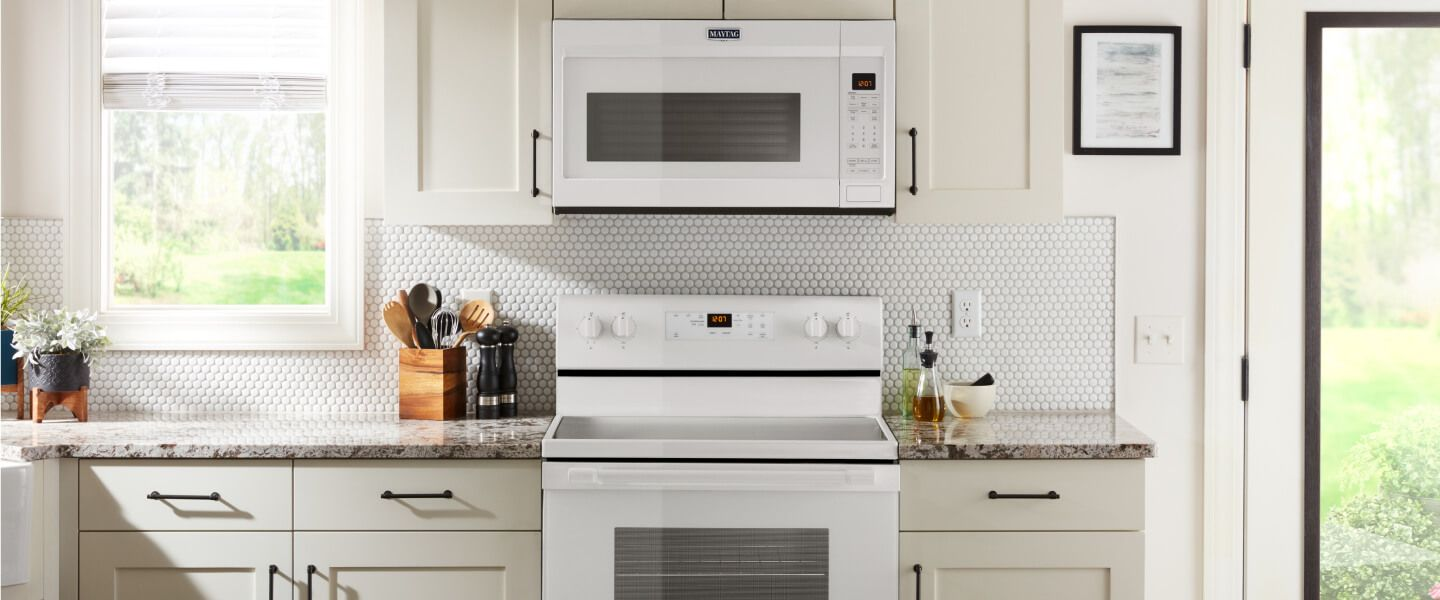 Front view of white kitchen with white Maytag® range and microwave