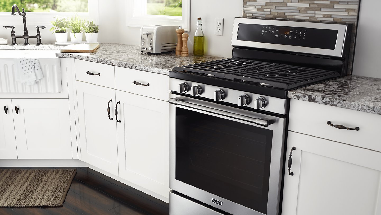 Maytag® gas range installed between white kitchen cabinets