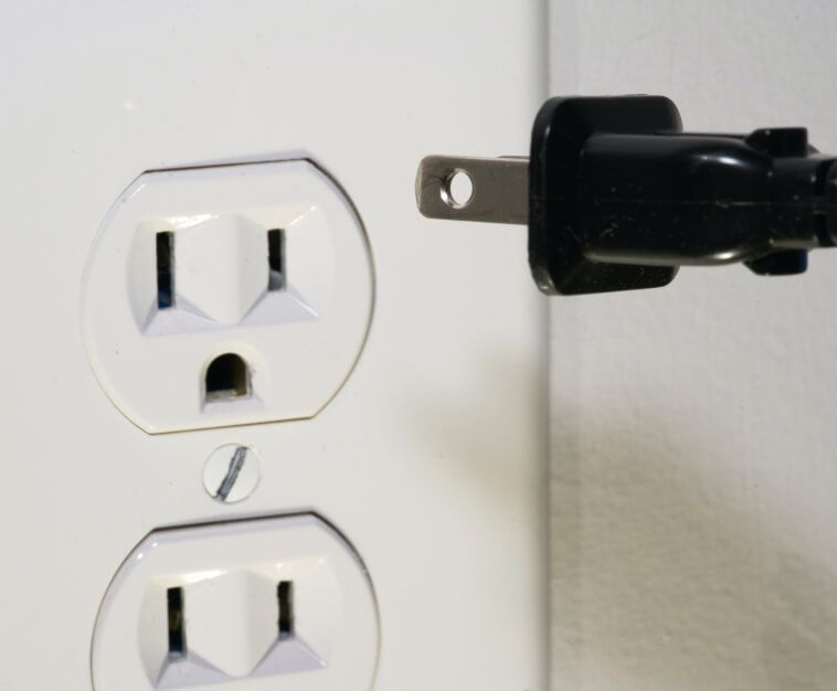 Power cord being unplugged from electrical outlet
