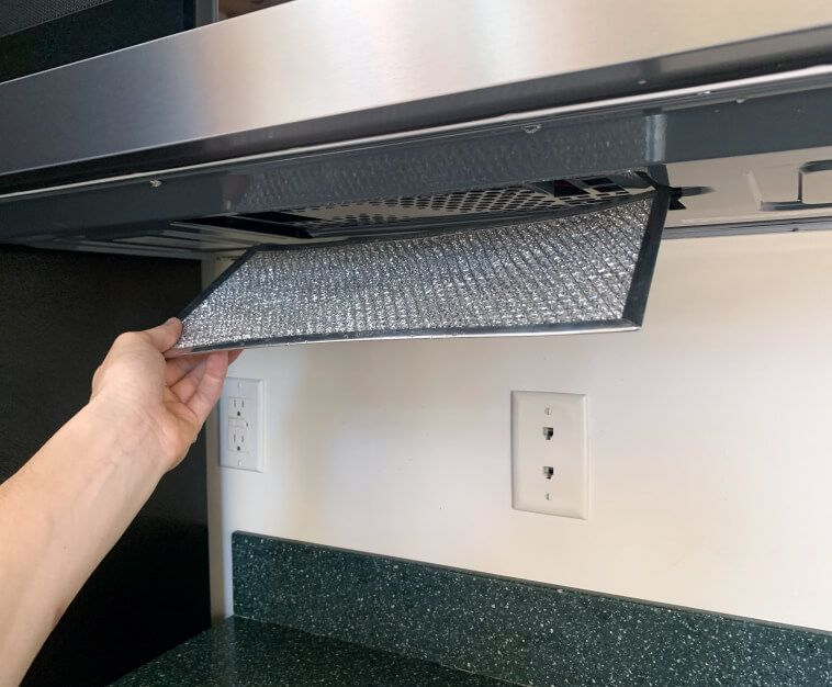 Hand removing grease filter from bottom of the microwave