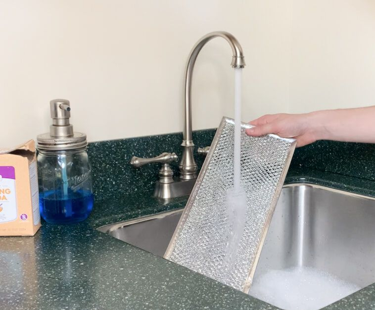 Grease filter being rinsed under a running faucet