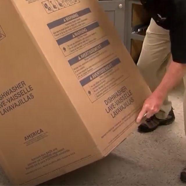 Installer cutting open dishwasher packaging