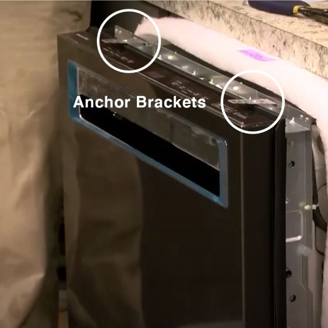 Dishwasher with anchor brackets attached to the top