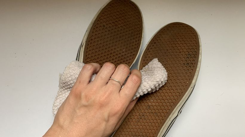 Hand wiping soles of shoes with towel