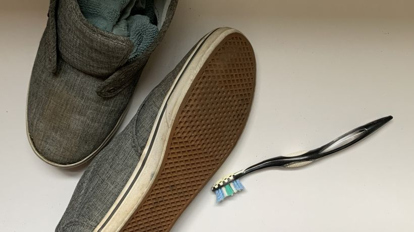 Shoes stuffed with rags next to a toothbrush