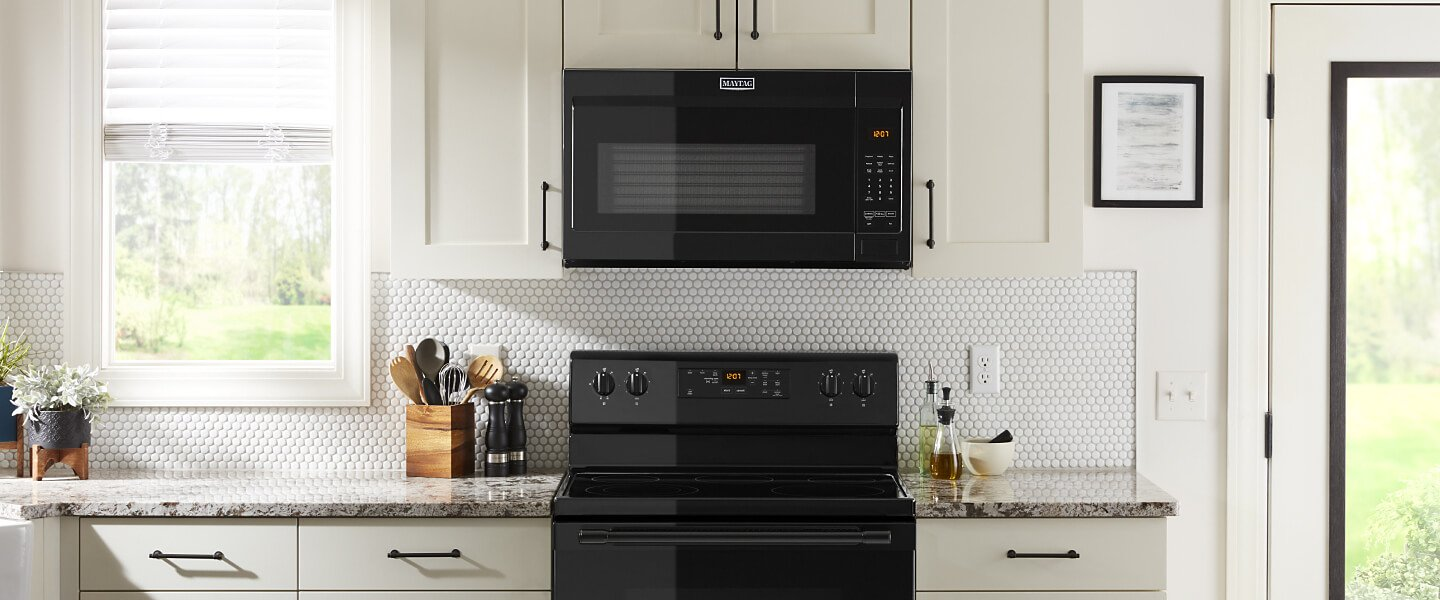 Black over-the-range microwave in white cabinets.