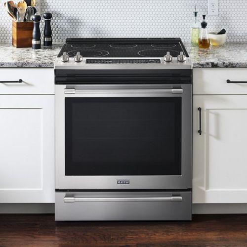 Slide-in electric range between cabinets