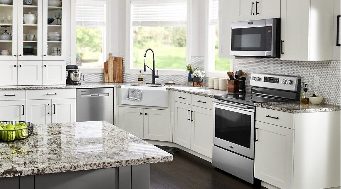 Large, white kitchen with stainless steel appliances