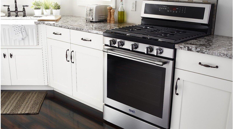 Freestanding gas range in a white kitchen
