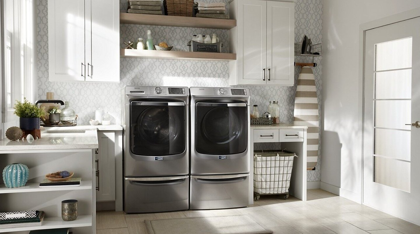 Maytag® washer and dryer on laundry pedestals in bright laundry room