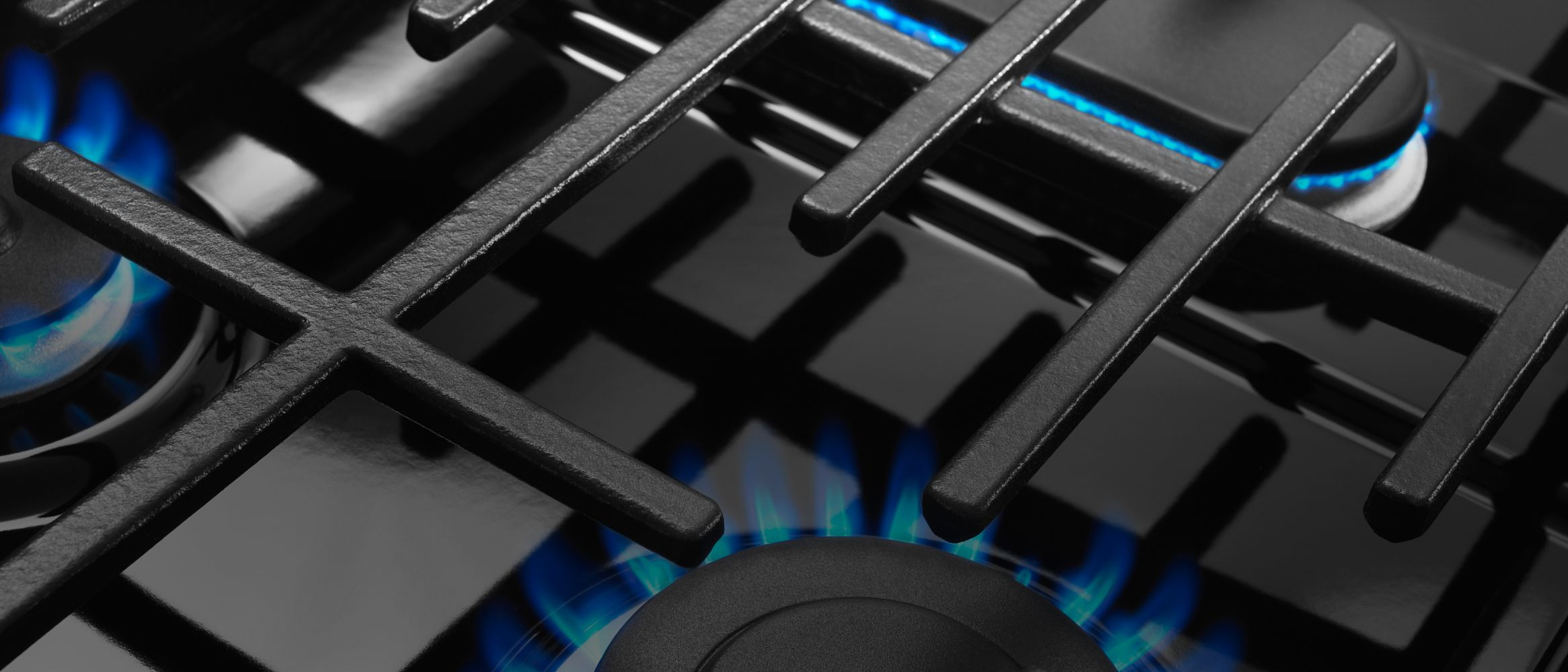 Lit burners on a Maytag® cooktop.
