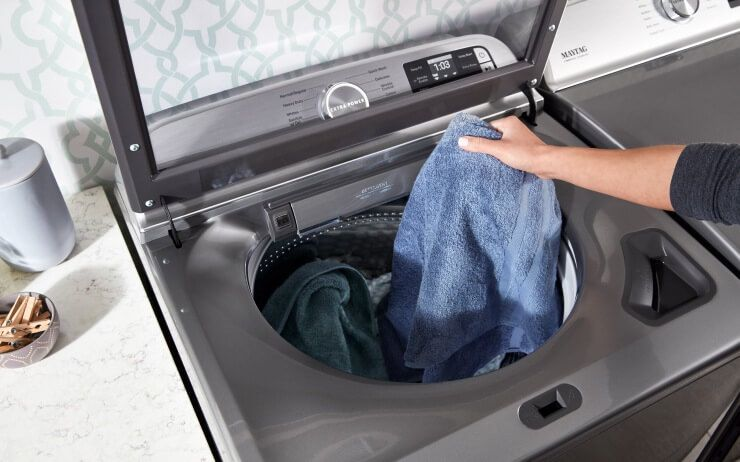 A Maytag® top load washer filled with blue clothes.